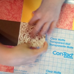 child's hands laying out scrapbook paper squares onto a grid to make a thanksgiving placemat