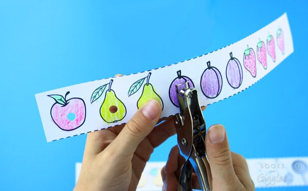 child's hands hole punching a strip of paper with fruit from the book The Very Hungry Caterpillar