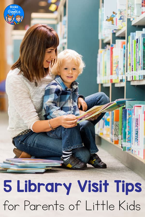 mom reading aloud to a little boy on her lap in a library