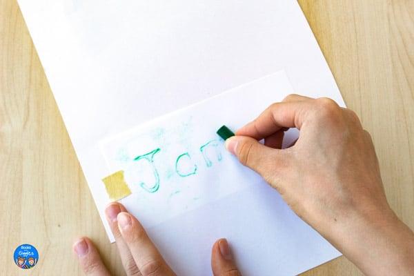 rubbing crayon on a name card