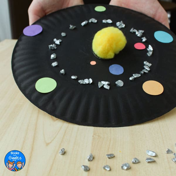 child's hands holding finished solar system craft up