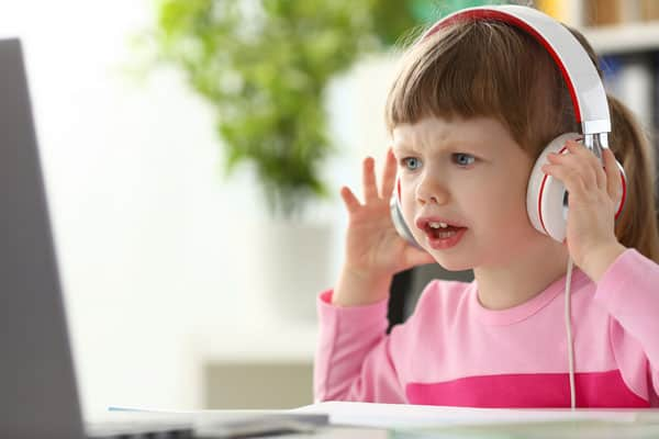 Little girl wearing headphones looking frustrated at a computer
