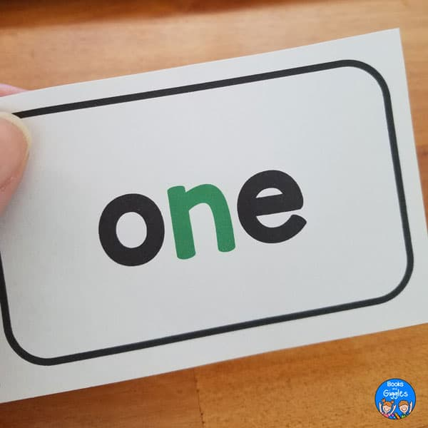"closeup of hand holding sight word flashcard for the word ""one"""