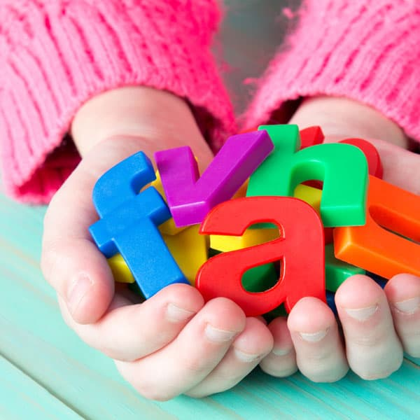 child's  hands holding plastic colorful letters