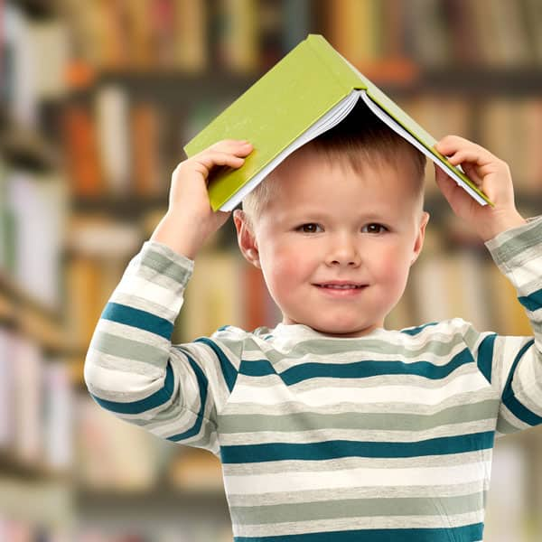 slightly smiling little boy with an open book atop his head, with bookshelves behind him