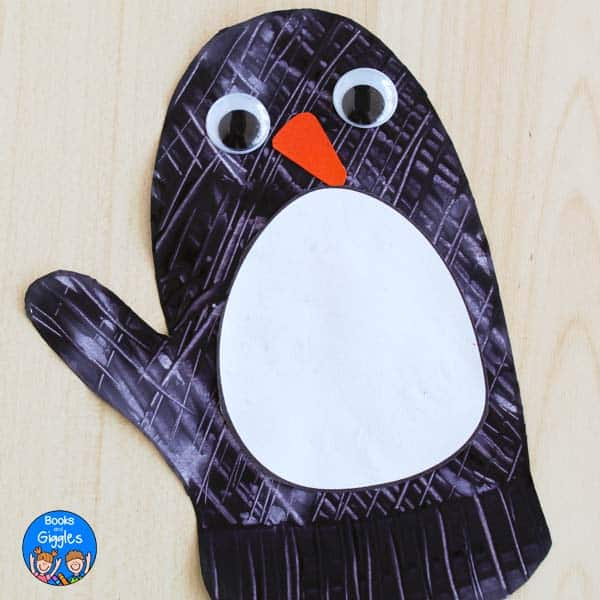 penguin mitten craft on a tabletop