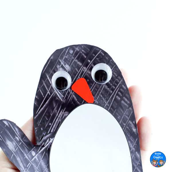 hand holding a penguin mitten craft