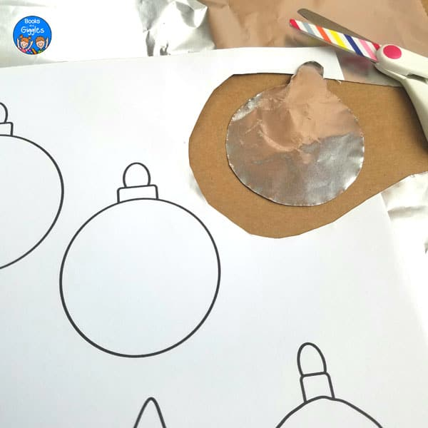 cut out foil ornament and printable ornament sheet next to child's scissors