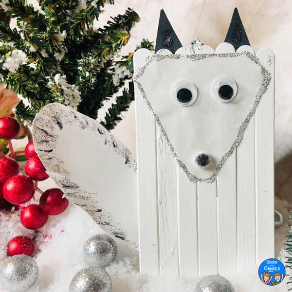 craft stick arctic fox displayed with decorative snow and berries