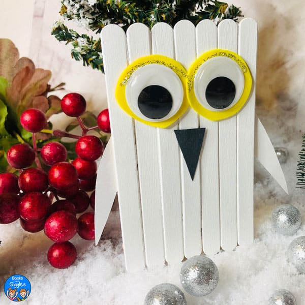 craft stick snowy owl displayed on styled background