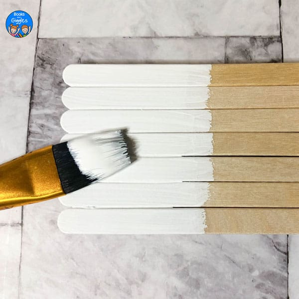paintbrush and popsicle sticks partly painted white