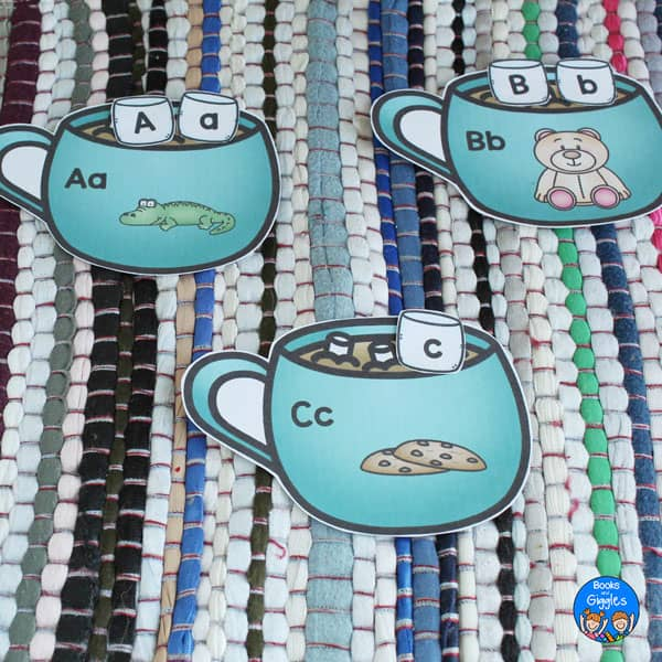 3 paper hot chocolate mugs with letter sound pictures and marshmallow letters, laid out on a multicolored mat