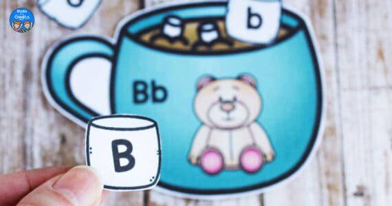 hand holding up a paper marshmallow with the letter B on it - cropped version