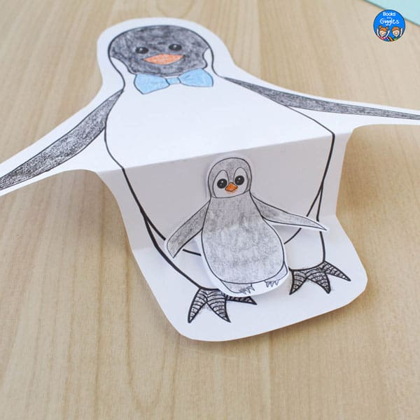 folded penguin craft with dad and chick colored in