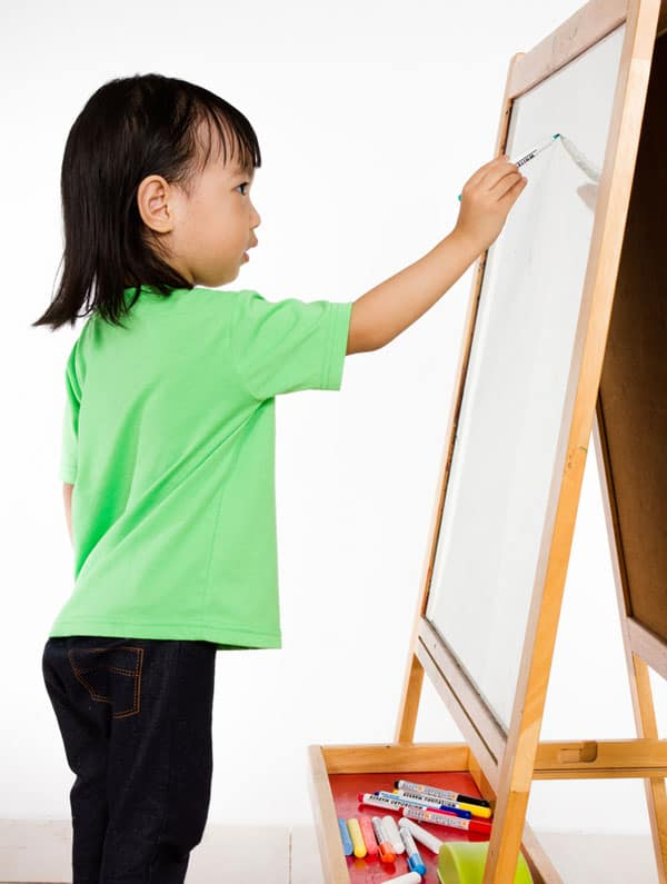 young child writing on an easel whiteboard with a dry erase marker