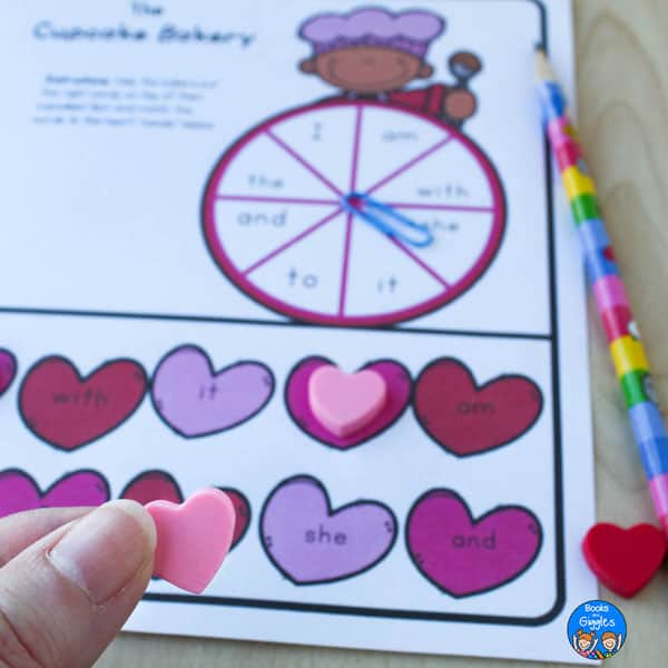 fingers holding a heart shaped mini eraser over a Valentine's Day sight word spinner activity