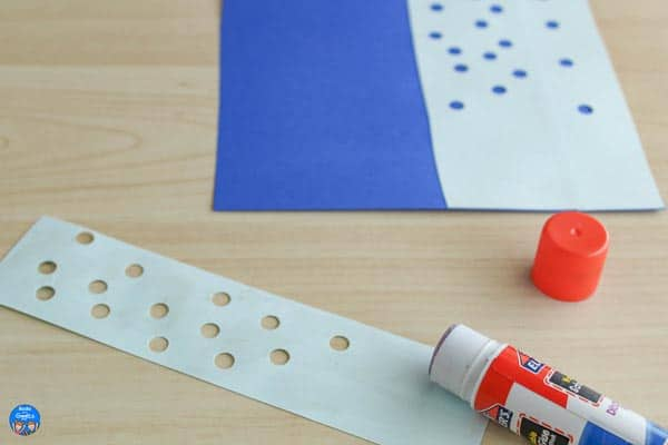 strip of light blue paper with holes punched in it and a glue stick next to it. Background shows similar paper strips glued down onto a dark blue background.