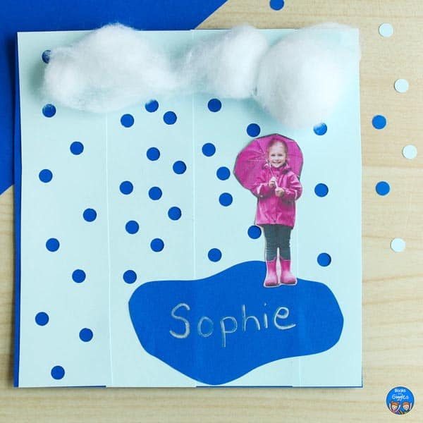 rain craft with hole punched rain, a puddle, cotton ball clouds, and a cutout photo of a girl holding an umbrella