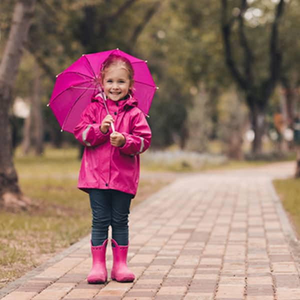 smiling little girl holding a pink umbrella and wearing a pink raincoat and boots
