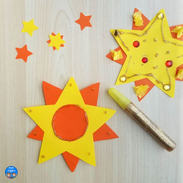 two yellow and orange paper sun crafts made with cutout stars, glitter glue, tissue paper, and plastic gems