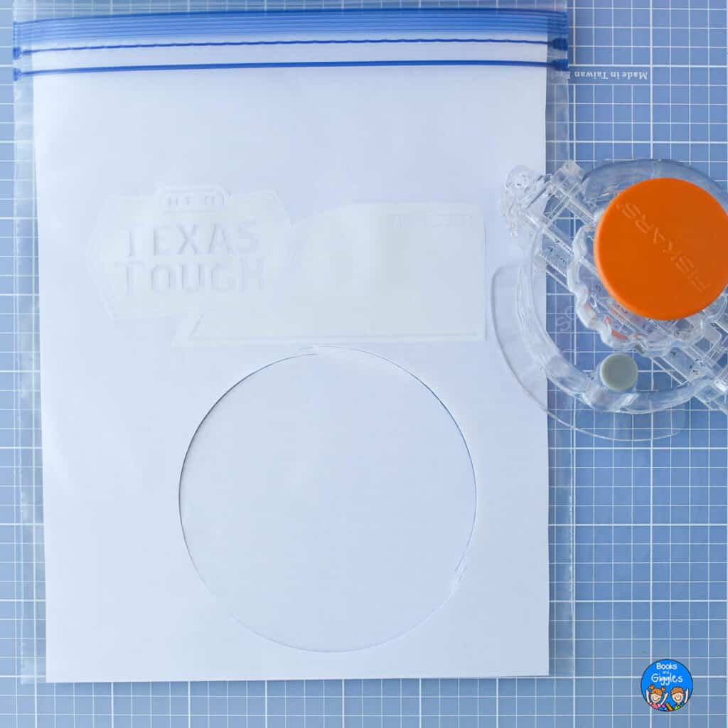 quart size ziptop bag with a circle cut into it and a circle cutter next to it, on a blue grid craft cutting board
