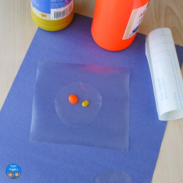 a dollop of orange and dot of yellow paint on a circle of plastic sitting on a square of contact paper