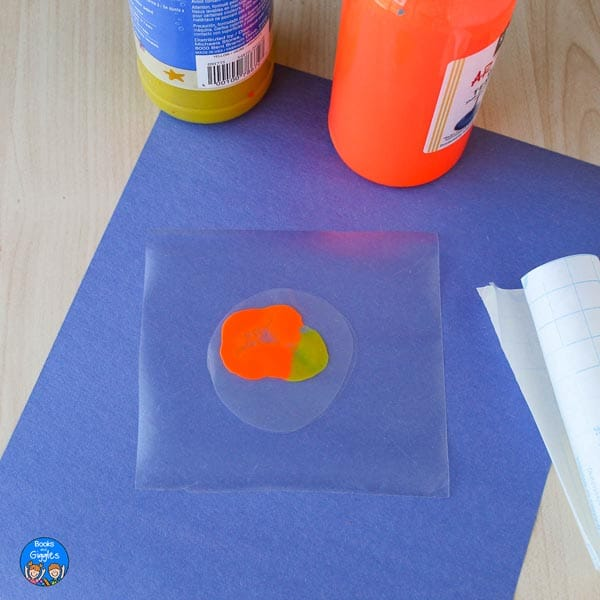 unmixed orange and yellow paint not yet completely sealed inside the contact paper
