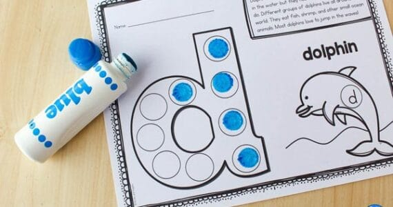 uncapped do-a-dot marker next to a worksheet with the letter d that is partly filled in with dots, and features a dolphin